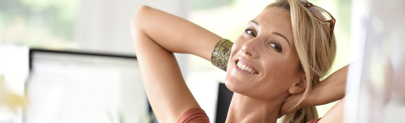 blonde Frau lehnt sich nach Brustvergrößerung in Moser Klinik lächelnd an Schreibtisch zurück