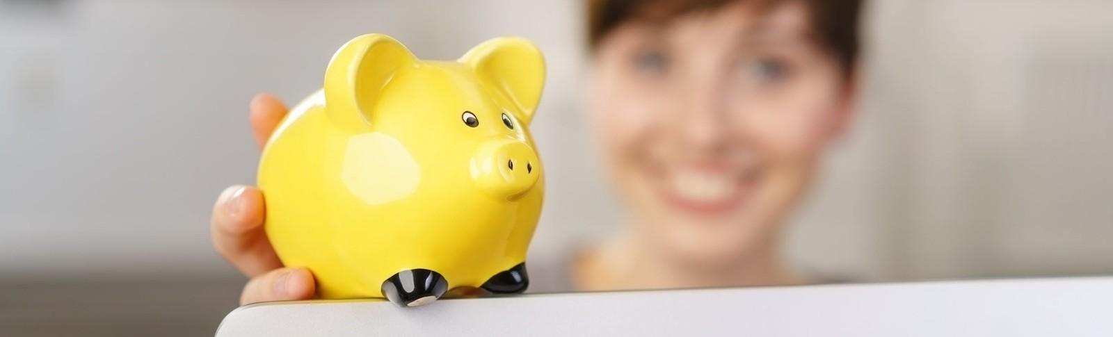 Frau hält gelbes Sparschwein in der Hand, denn in den Moser Kliniken kann sie ihre Bauchdeckenstraffung auf Raten bezahlen