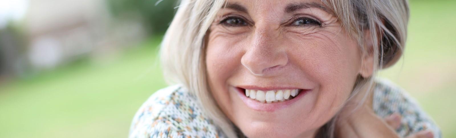 Frau lächelt wieder nach einer Faltenbehandlung  in den Moser Kliniken