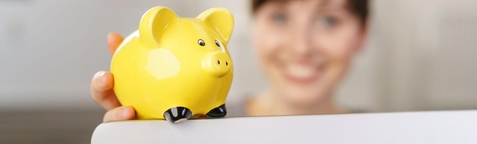 Frau hält gelbes Sparschwein in der Hand, denn in den Moser Kliniken kann sie ihre Fettabsaugung auf Raten bezahlen