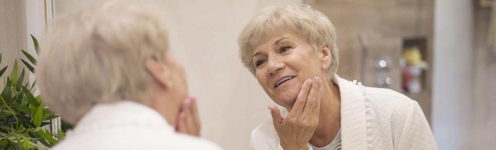 Ältere Frau betrachtet das Ergebnis ihrer Eigenfettunterspritzung im Gesicht in den Moser Kliniken im Spiegel
