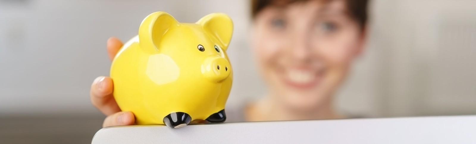 Frau hält gelbes Sparschwein in der Hand, denn in den Moser Kliniken kann sie ihre Bruststraffung auf Raten bezahlen