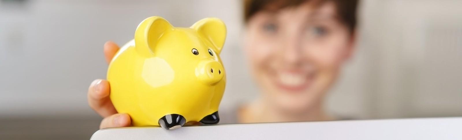 Frau hält gelbes Sparschwein in der Hand, denn in den Moser Kliniken kann sie ihre Brustverkleinerung auf Raten bezahlen