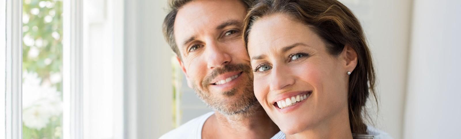Paar lächelt zufrieden in die Kamera - nach einer erfolgreichen Augenlidstraffung in den Moser Kliniken