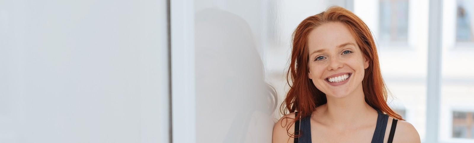 rothaarige Frau steht in Tür und freut sich, nachdem sie sich ihre Brustimplantate in der Moser Klinik entfernen gelassen hat.