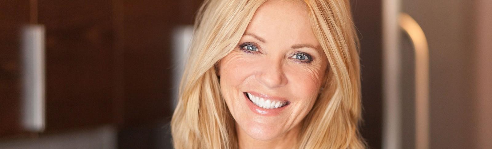 Blonde Frau lächelt nach erfolgreicher Tränensack OP bei den Moser Kliniken in die Kamera