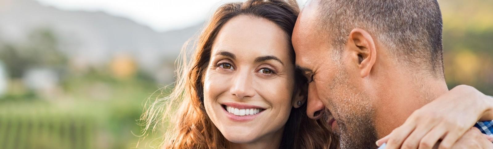 Eine Patientin der Moser Kliniken umarmt nach einer Augenlidstraffung in Augsburg ihren Partner und lächelt in die Kamera