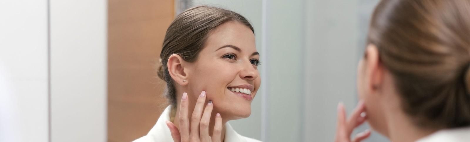 Frau betrachtet das Resultat ihrer Ohrenkorrektur in den Moser Kliniken