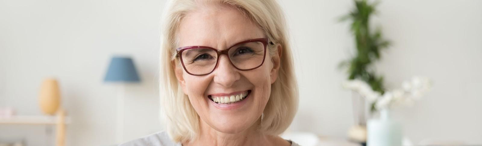 Blonde Frau mit Brille kann nach Unterspritzung der Nasolabialfalte wieder freudig lächeln