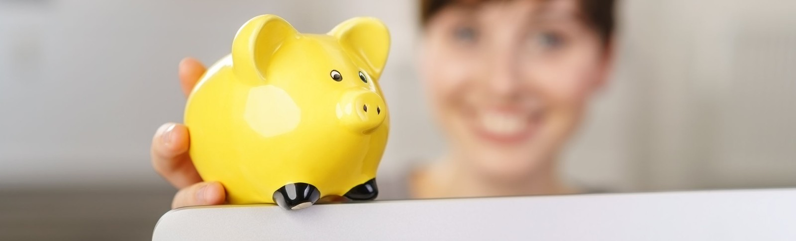 Frau hält gelbes Sparschwein in der Hand, denn in den Moser Kliniken kann sie ihre Haartransplantation auf Raten bezahlen