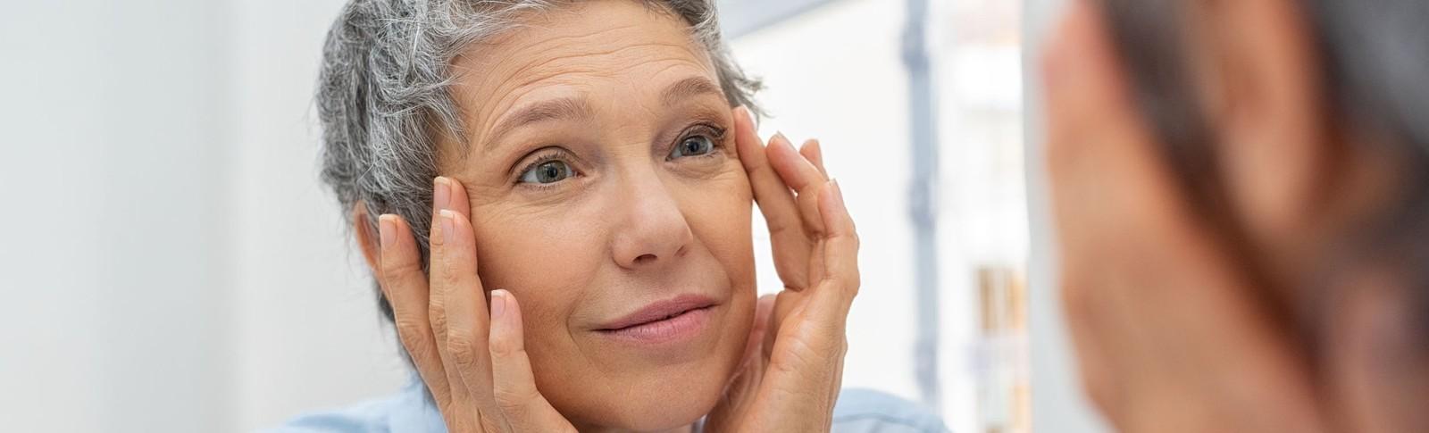 Frau betrachtet das Ergebnis der Gesichtsstraffung in den Moser Kliniken im Spiegel.