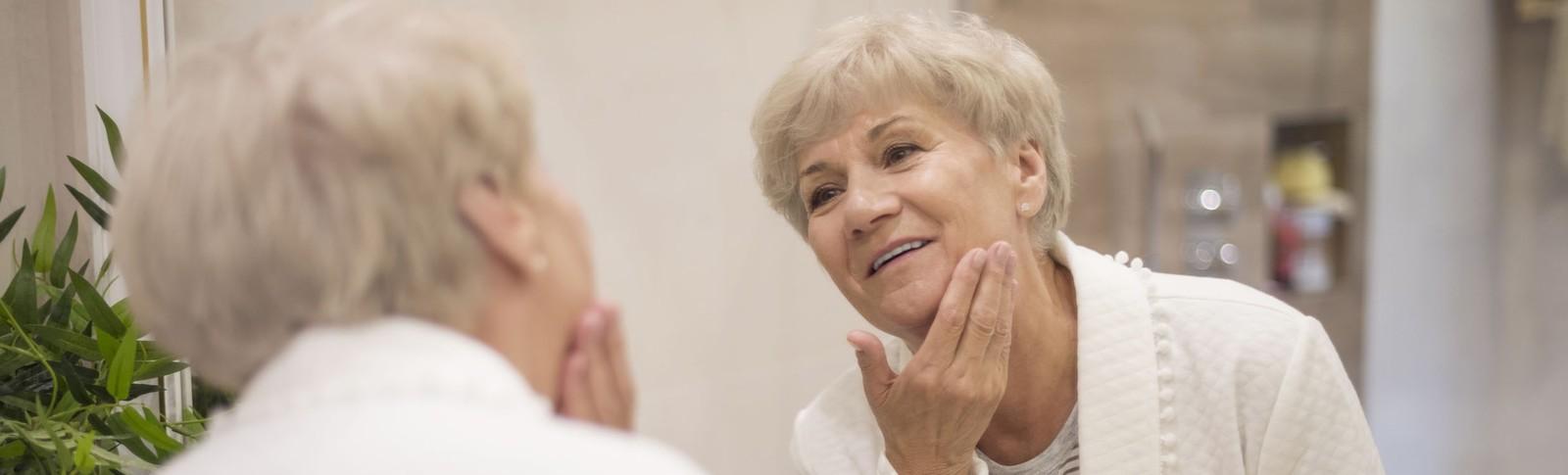 Ältere Patientin betrachtet sich nach einem Wangenlifting in den Moser Kliniken im Spiegel