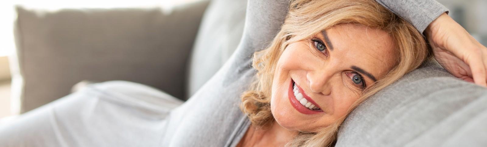 auf Sofa liegende Frau ist glücklich über ihre Brustverkleinerung in der Moser Klinik